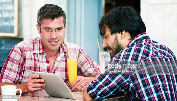 Young man showing media to friend with tablet at cafe