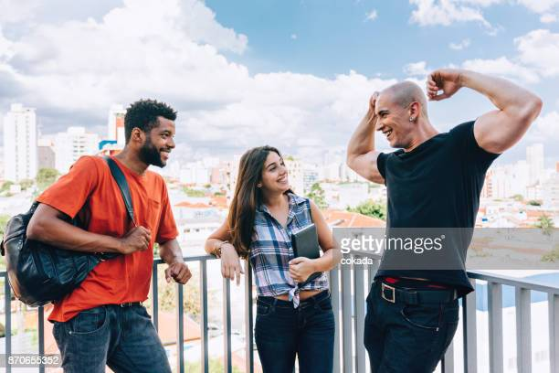 young man showing off his muscles to his friends - showing off stock pictures, royalty-free photos & images