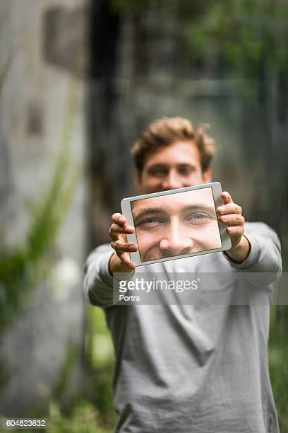 Young man showing photograph on digital tablet. Selfie