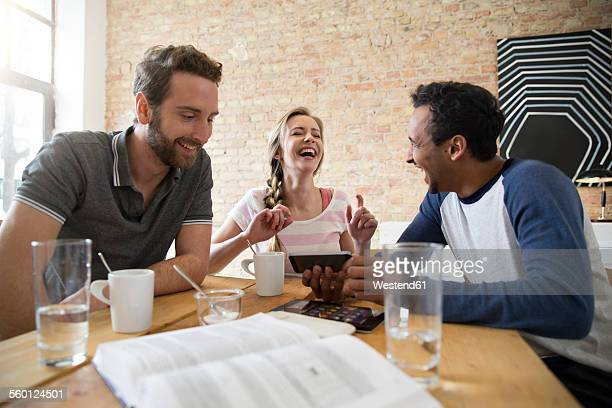 Young man showing smartphone to friends