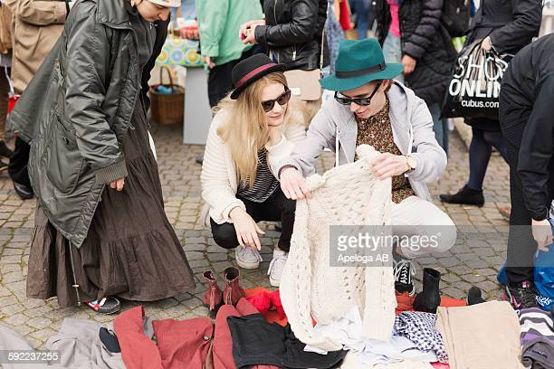 Young man showing sweater to friend while shopping at flea market