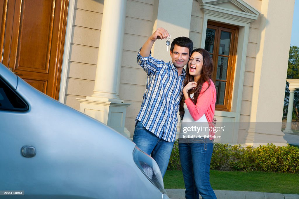 Young man shows car keys to young woman : Stock Photo