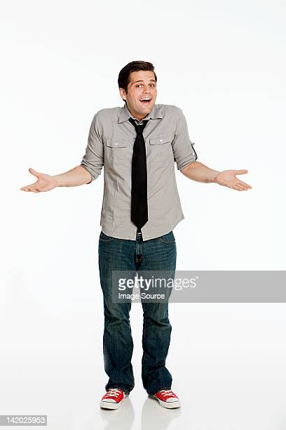Young man shrugging shoulders against white background