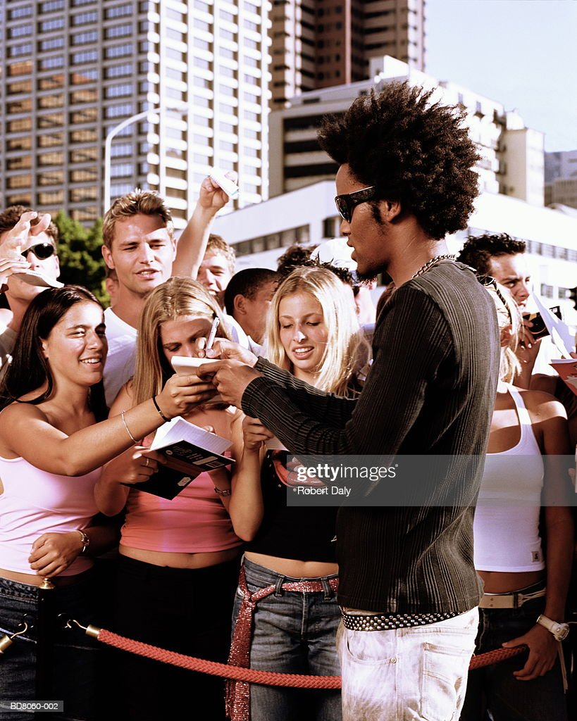 Young man signing autographs for fans : Stock Photo
