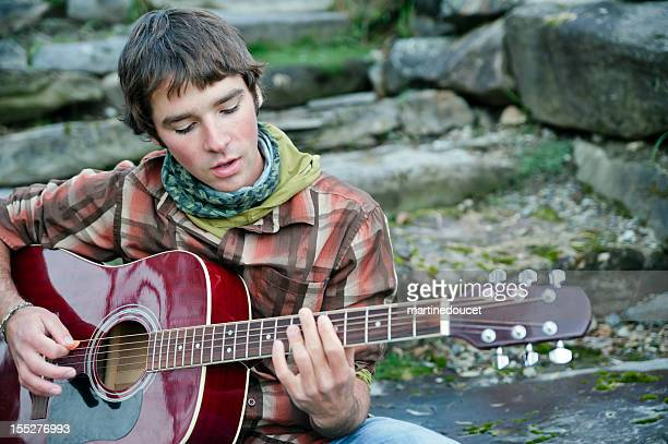 Young man singing and playing acoustic guitar.