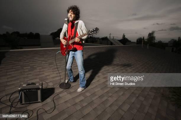 young man singing into a microphone - verstärker stock-fotos und bilder