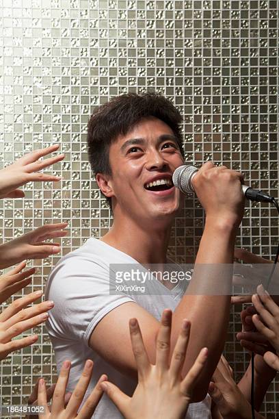 Young man singing into a microphone with lots of hands reaching for him