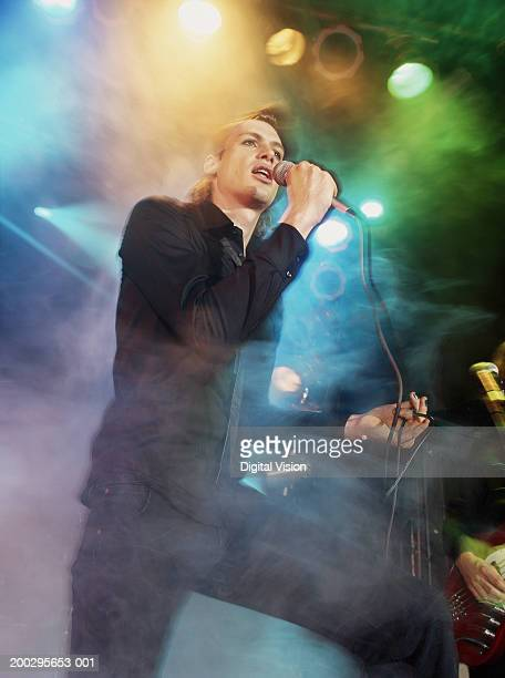 Young man singing into microphone on stage, low angle view