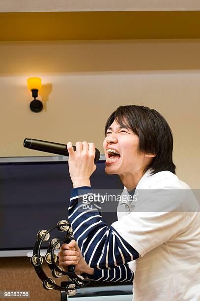 Young man singing karaoke