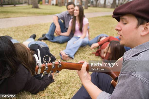 Young man singing to friends on campus