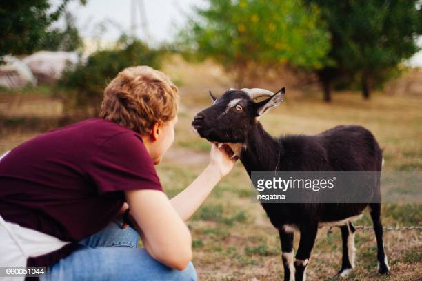 young man sit and stroke the black goat