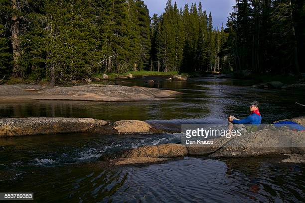 a young man sits by the river in tuolumne meadows. - riverbank stock pictures, royalty-free photos & images