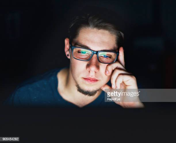 young man sits in the dark staring at computer monitor - cyberbullying stock photos and pictures
