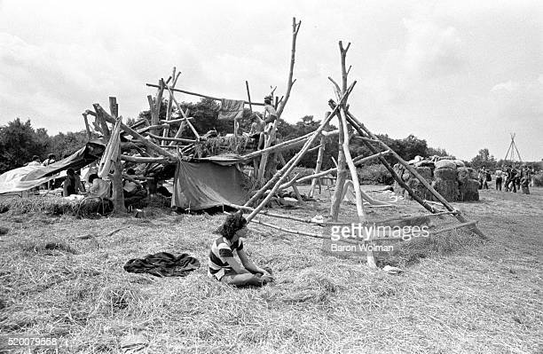 A young man sits next to a handmade wooden tent at the Woodstock Music Art Fair Bethel NY August 15 1969