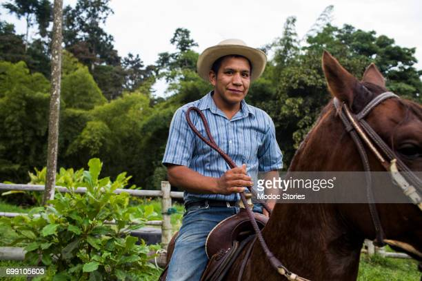 A young man sits on a horse and smiles on a coffee farm in Colombia.