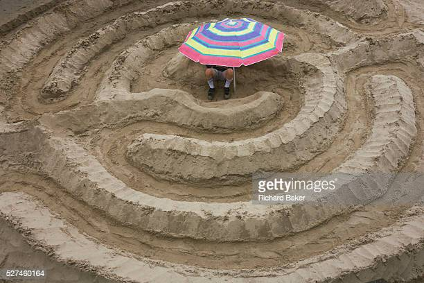A young man sits on a sandbank beneath a sun brolley With legs and feet protruding the man is in the middle of a sand maze constructed for the London...