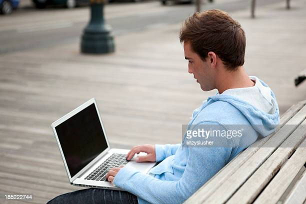 Young man sits on park bench using laptop