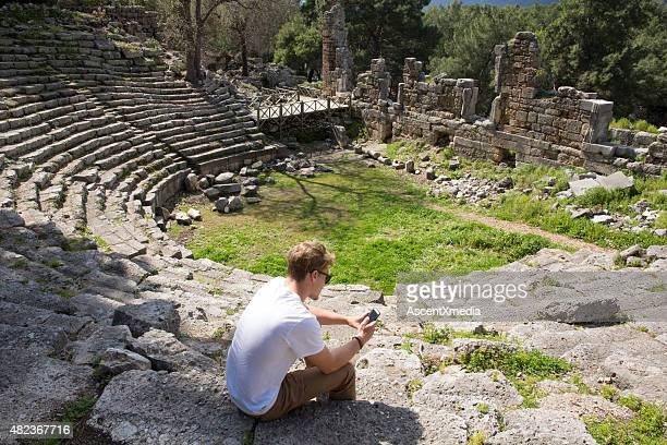 Young man sits on theatre steps of ancient Greek ruin