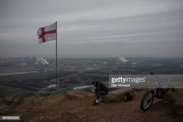 A young man sits on top of Eston Nab in North Yorkshire which looks down at the view over the industrial area of Teeside and Middlesbrough on...