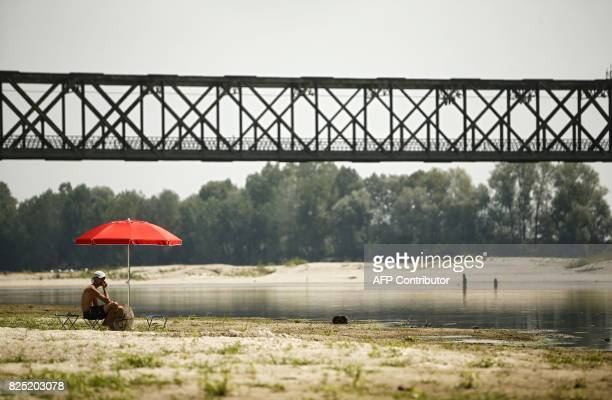 A young man sits under an umbrella at the Po River near the Ponte della Becca bridge in Linarolo near Pavia northern Italy on August 1 as the country...