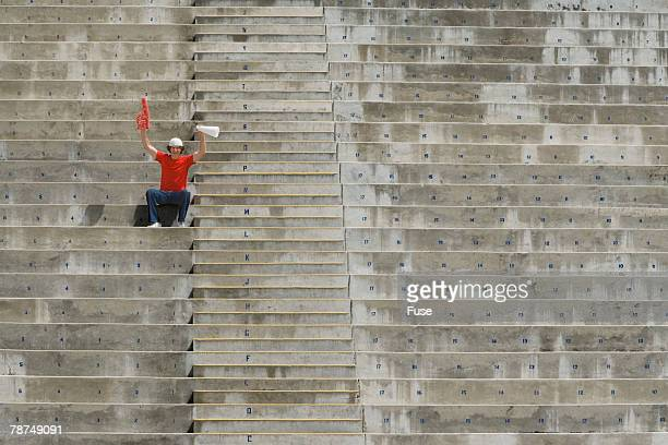young man sitting alone in bleachers - foam finger stock photos and pictures