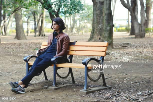 young man sitting alone - ベンチ ストックフォトと画像