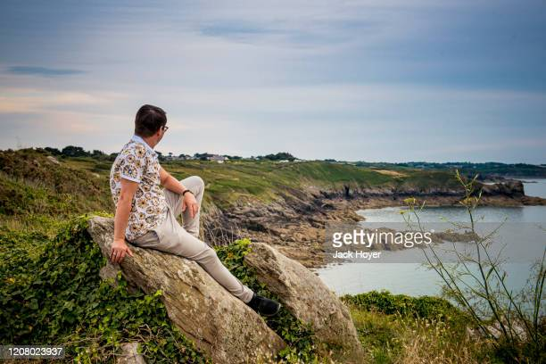 young man sitting an the cliff line in dusk - エウロパ ストックフォトと画像