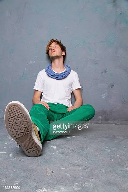 Young man sitting and leaning agaist dirty wall, portrait