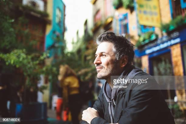Jeune homme assis et se détendre à la table au centre de ville de Paris