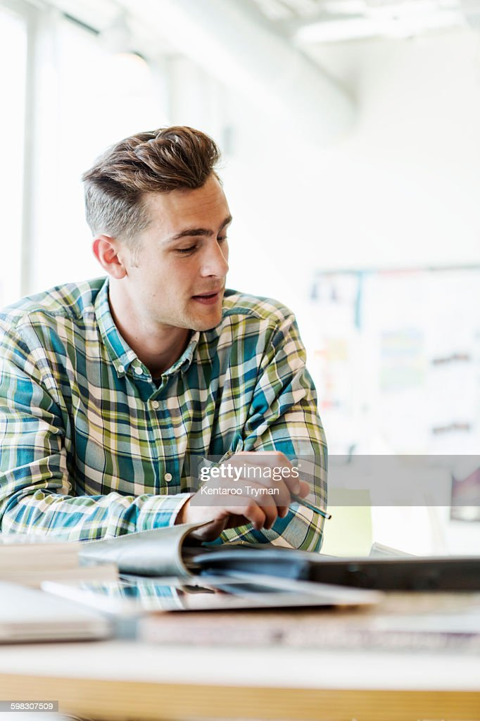 Young man sitting and studying in classroom : Stock Photo