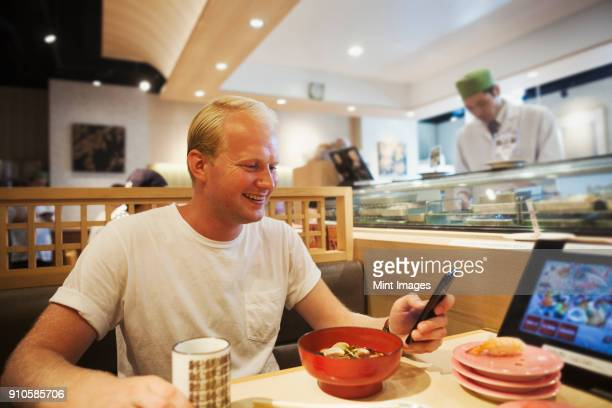 Young man sitting at a table in an Asian Fast Food restaurant, looking at smartphone, smiling.