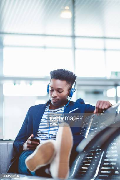 Young man sitting at airport waiting area and listening to music