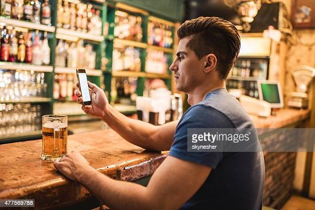 Young man sitting at bar counter and using mobile phone.