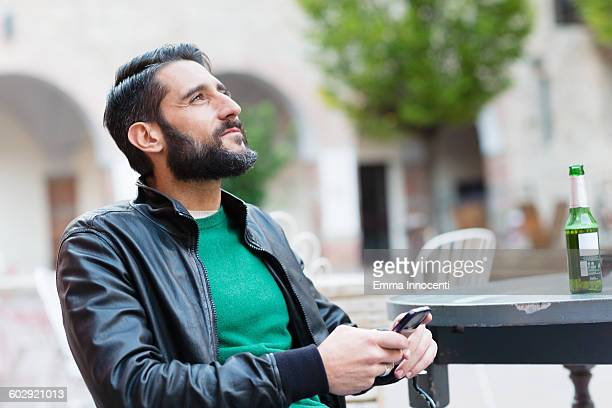 young man sitting at caffe texting and drinking