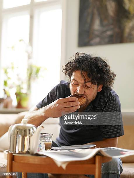 young man sitting at coffetable, eating croissant - french culture stock pictures, royalty-free photos & images