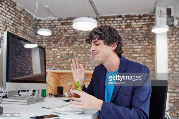 Young man sitting at desk, eating sandwich