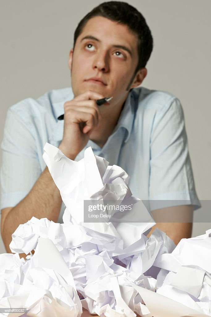 Young man sitting at desk with crumpled paper : Stockfoto