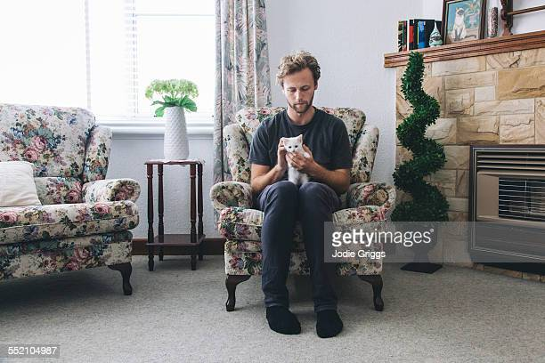 Young man sitting at home with small white kitten