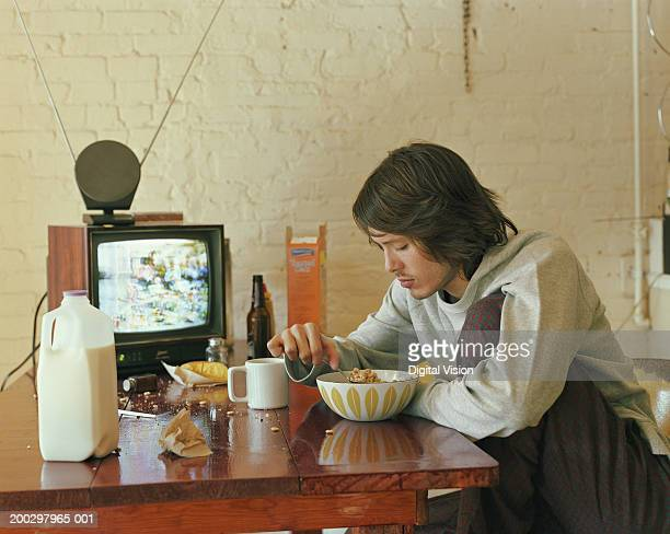 Young man sitting at kitchen table eating breakfast cereal