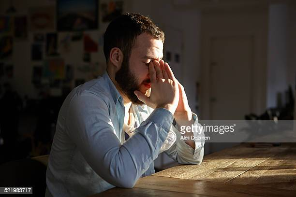 young man sitting at kitchen table with hands on face - verdriet stockfoto's en -beelden