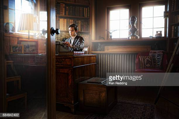 Young man sitting at old-fashioned desk using vintage typewriter in 1920s-era library