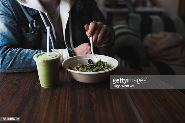 Young man sitting at table, eating salad, mid section