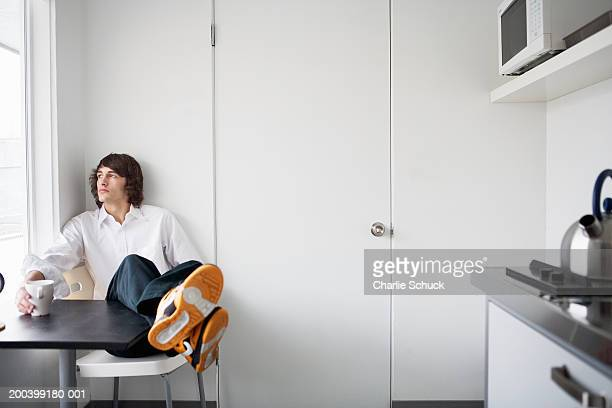 young man sitting at table in domestic kitchen, looking out window - colletto aperto foto e immagini stock