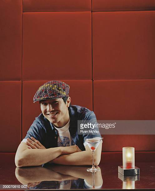 Young man sitting at table in nightclub, smiling, portrait