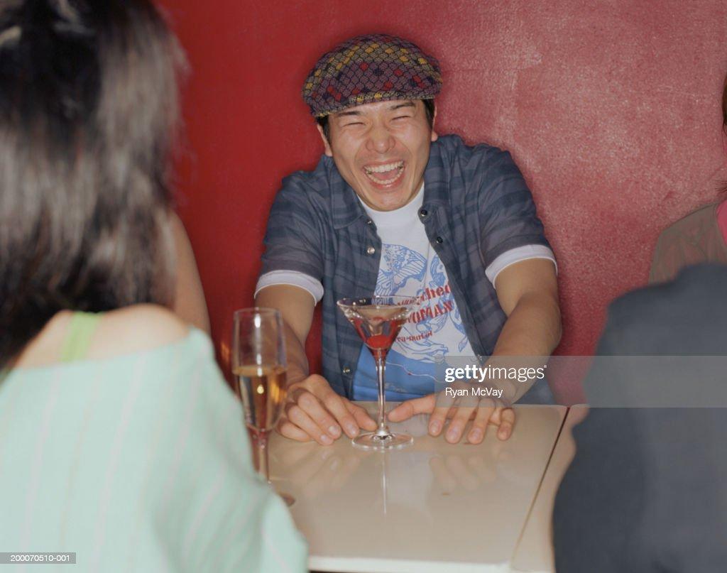 若い男性のラウンジで、ご友人とご一緒にテーブルのナイトクラブ、笑う : ストックフォト