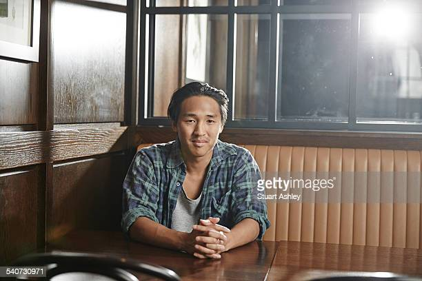 Young man sitting at table, wood tones