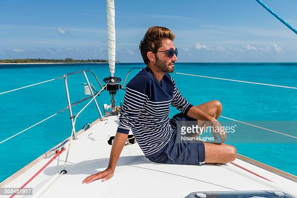 young man sitting at the bow of sailboat