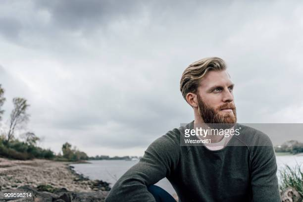 young man sitting at the river in autumn, portrait - facial hair stock pictures, royalty-free photos & images