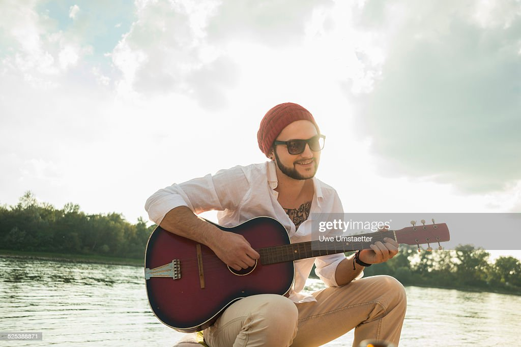 Young man sitting by lake playing guitar : Stock Photo