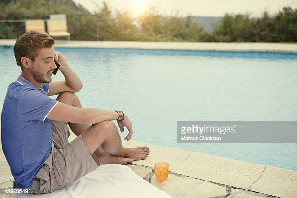 young man sitting by the pool on his phone - blue shorts stock pictures, royalty-free photos & images